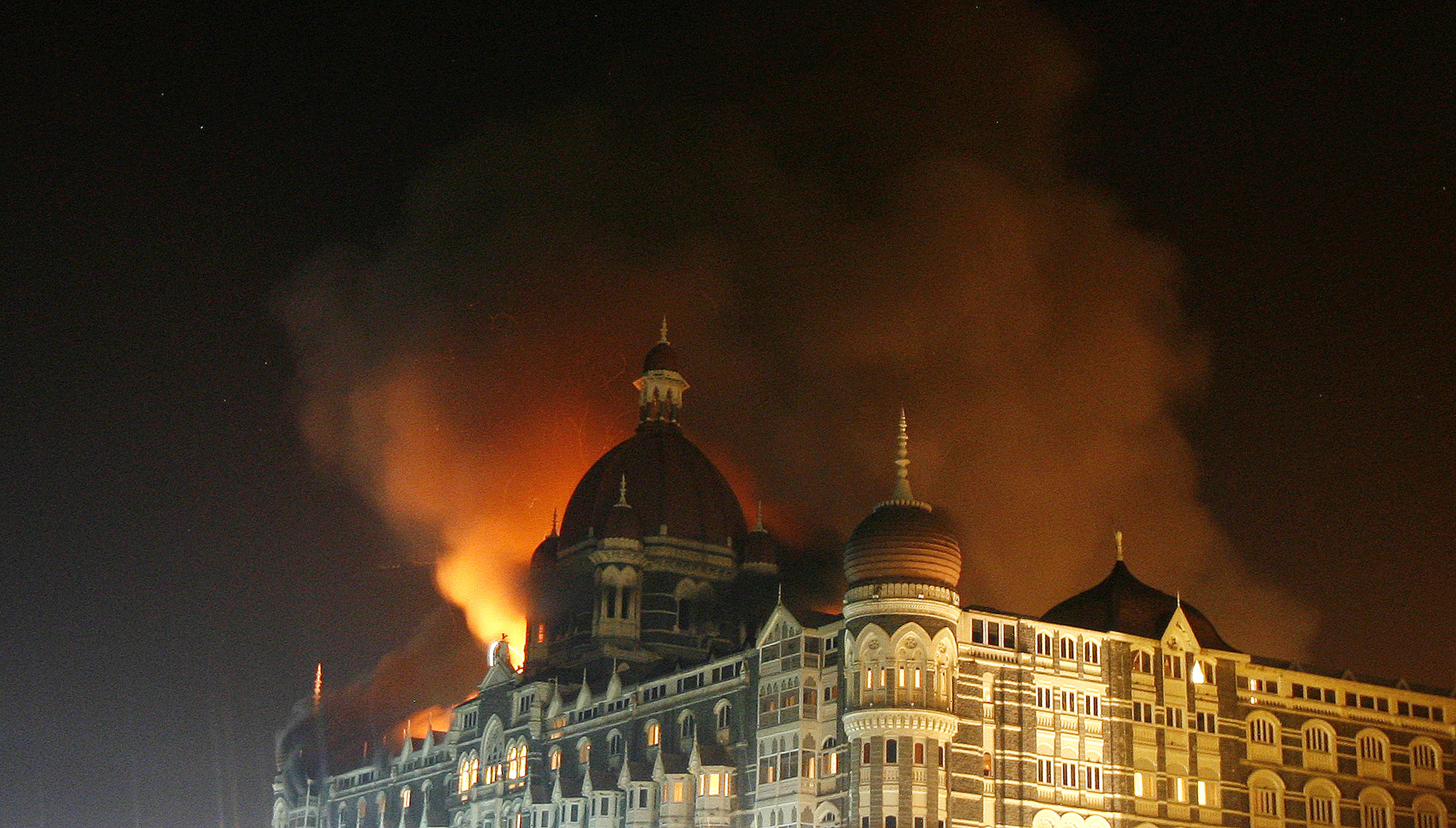Smoke rises from the Taj Hotel in Mumbai November 27, 2008. Gunmen killed at least 80 people in a series of attacks in India's financial capital Mumbai and troops began moving into one of two five-star hotels on Thursday where Western hostages were being held, local television said. REUTERS/Arko Datta (INDIA) - RTXAZZ1