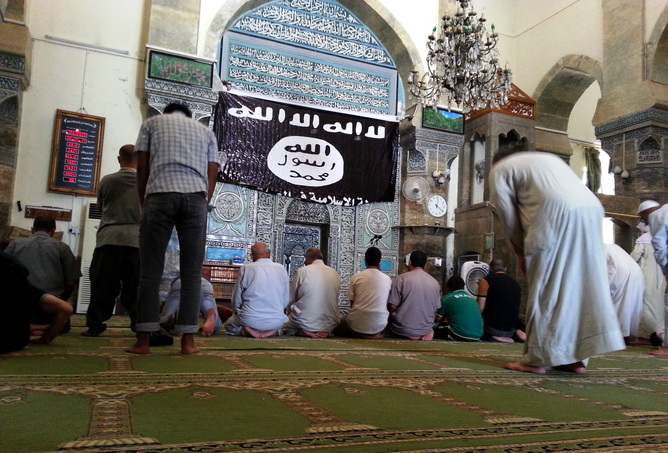 epa04307451 Worshipers pray at the Al-Noori Al-Kabeer mosque, next to flag used by the Islamic State (IS), in Mosul city, northern Iraq, 09 July 2014. Abu Bakr al-Baghdadi, the leader of the Sunni extremist group Islamic State appeared for the first time on 04 July at Al-Noori Al-Kabeer mosque in Mosul city, as he was purportedly delivering the noon prayer's sermon. Fighters of IS, an al-Qaeda splinter group, have in recent weeks seized large parts of northern and western Iraq, including Mosul, and made a swift advance to capture a string of towns stretching south towards Baghdad.  EPA/STR