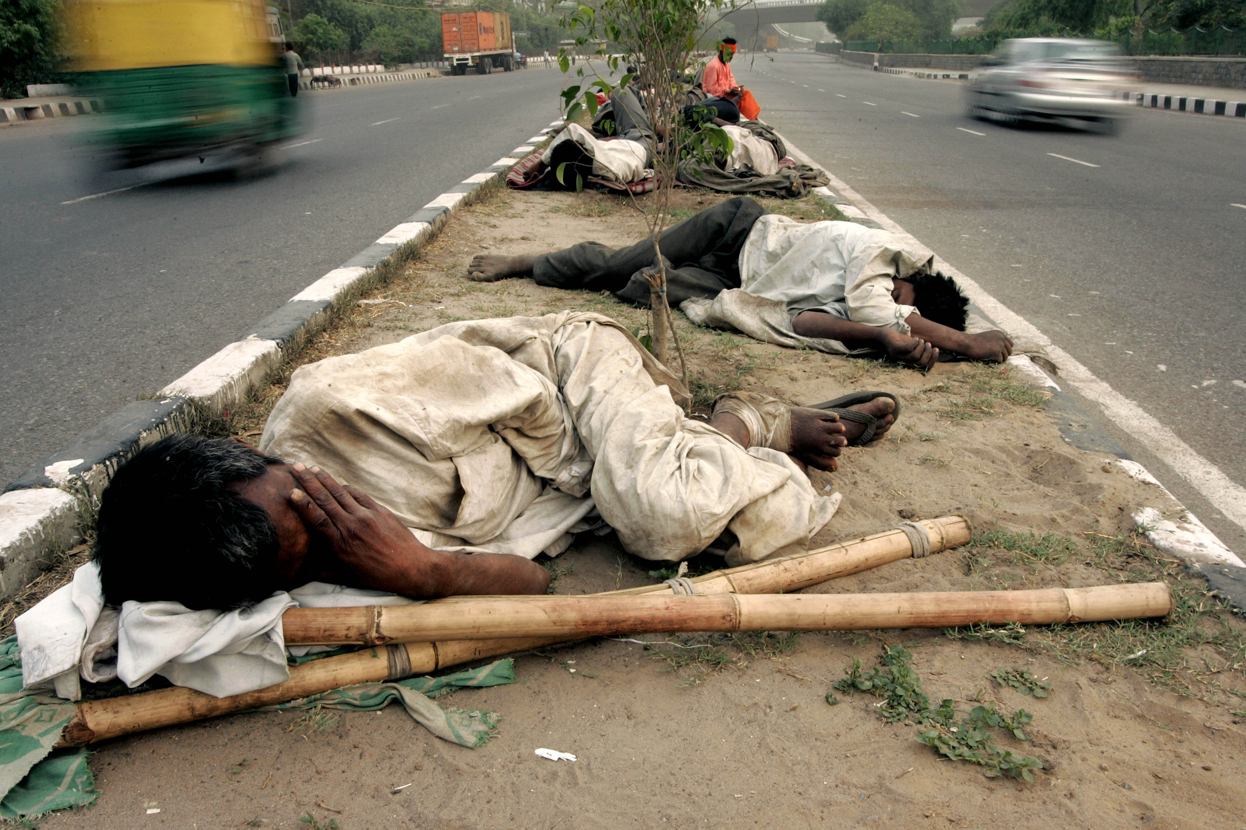 Homeless Indians sleep on a pavement of New Delhi, April 26, 2006. Global poverty rates have fallen by as much as 10 percent over the past five years with the biggest declines in India and China, which account for about one in three people in the world, the World Bank said.   REUTERS/Kamal Kishore - RTR1CT65