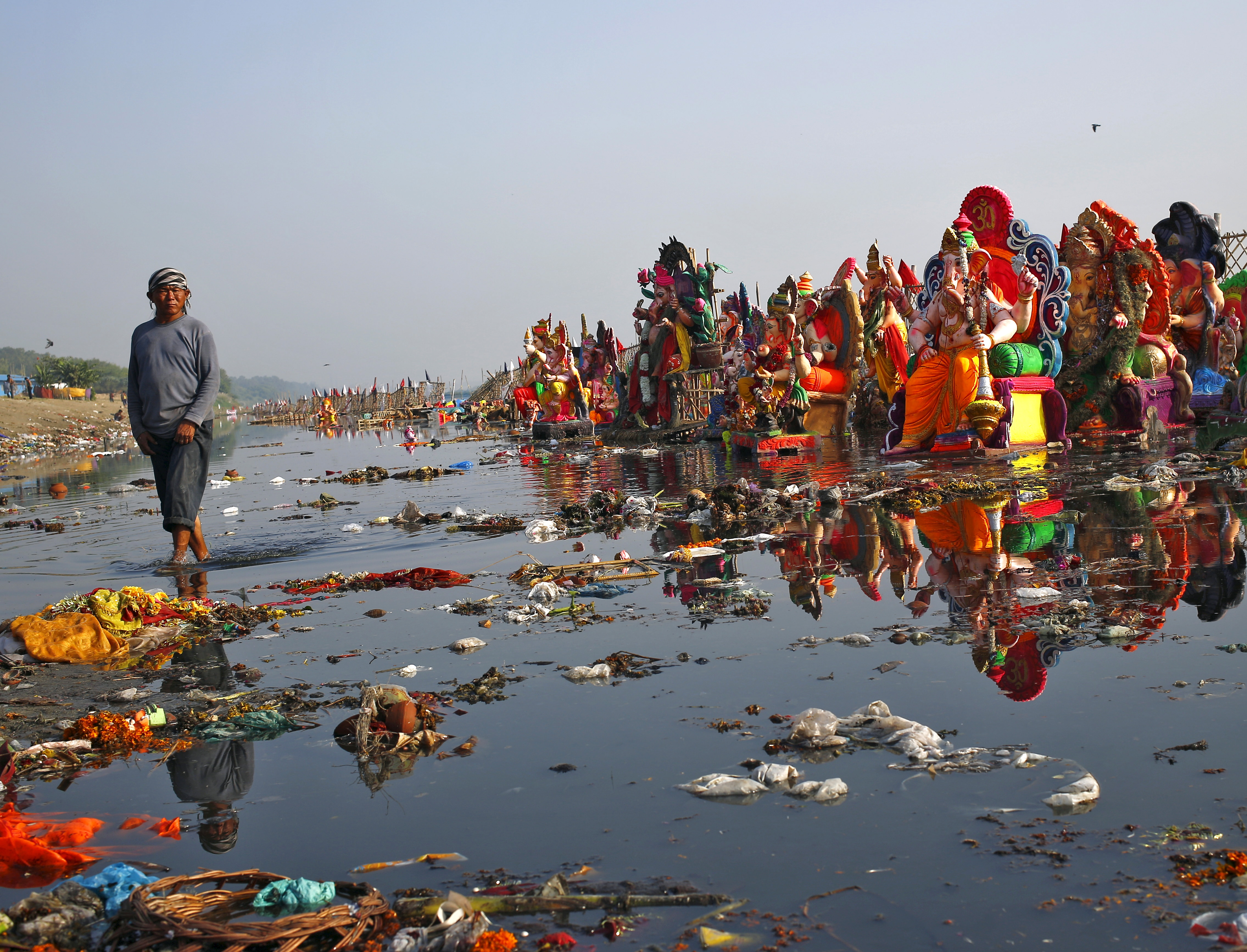 Man looks on as he collects items thrown by devotees as religious offerings next to idols of Hindu god Ganesh in waters of Yamuna river in New Delhi