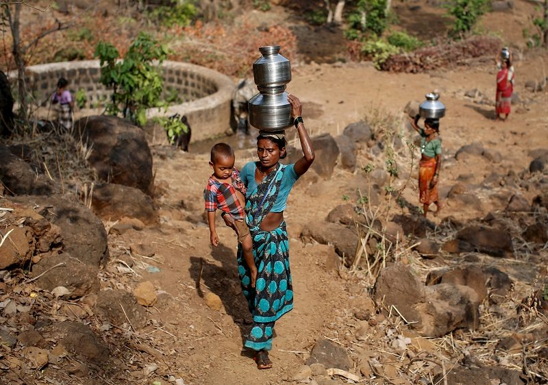 """Shivarti, the second wife of Namdeo, holds her grandson while carrying metal pitchers filled with water from a well outside Denganmal village, Maharashtra, India, April 21, 2015. In Denganmal, a village in Maharashtra state, some men take a second or third wife just to make sure their households have enough drinking water. Becoming what are known as """"water wives"""" allows the women, often widows or single mothers, to regain respect in conservative rural India by carrying water from the well quite some distance from the remote village. When the water wife, who does not usually share the marital bed, becomes too old to continue, the husband sometimes takes a third and younger spouse to fetch the water in metal pitchers or makeshift containers. REUTERS/Danish Siddiqui TPX IMAGES OF THE DAY PICTURE 22 OF 29 FOR WIDER IMAGE STORY """"WATER WIVES OF MAHARASHTRA""""??SEARCH """"WATER WIVES"""" FOR ALL IMAGES TPX IMAGES OF THE DAY - RTX1F2PH"""