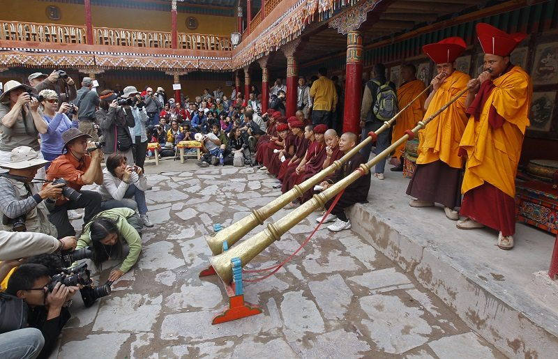 People take pictures of two monks play traditional bugle during the opening ceremony on the first day of two-day festival in Hemis Gompa, 45 km (28 miles) southeast of Leh July 10, 2011. The Hemis Gompa is the oldest and biggest monastery in Ladakh. The annual festival celebrates the birth anniversary of Guru Padmasambhava, the founder of Lamaism (an off-shoot of Buddhism) in the eighth century. The two-day festival is marked by ritual dancing in which dancers wear masks representing deities and evil spirits. REUTERS/Fayaz Kabli (INDIAN-ADMINISTERED KASHMIR - Tags: RELIGION SOCIETY) - RTR2OPFO