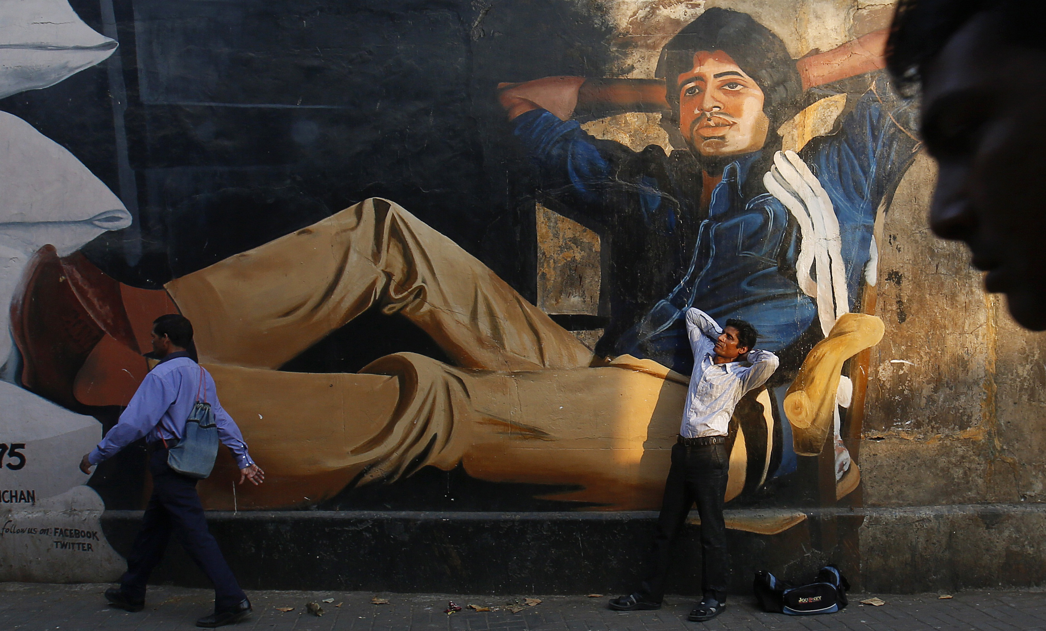 An aspiring actor, poses in front of a mural of Amitabh Bachchan in Mumbai