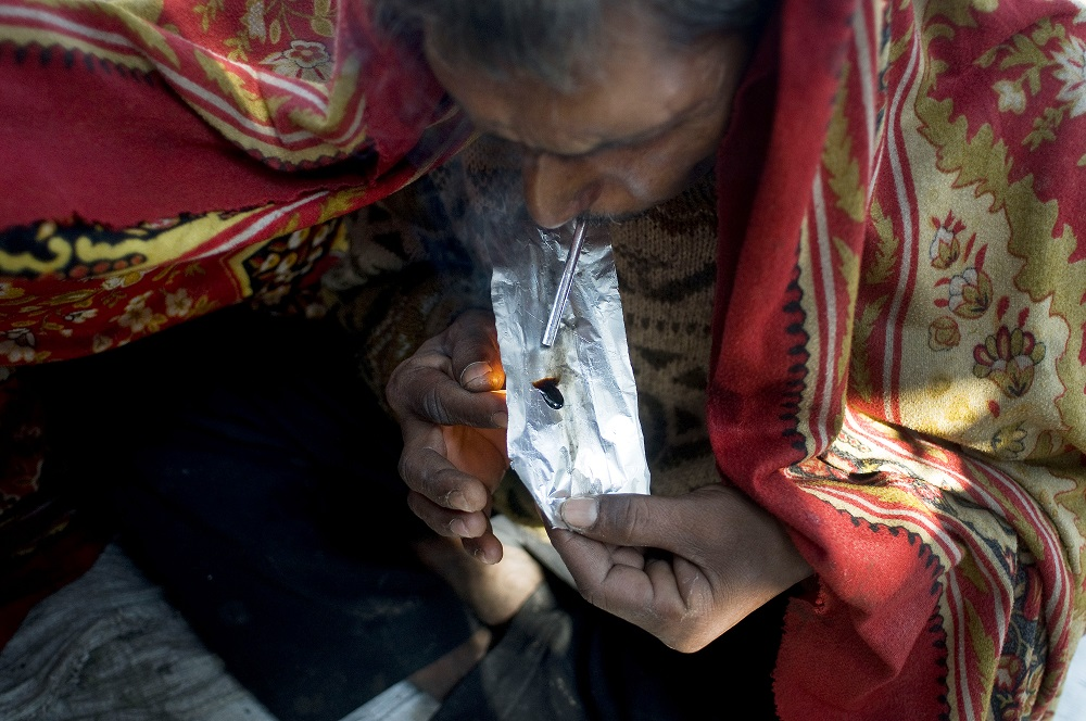 An Indian drug user covers himself with a blanket as he smokes smack,heroin, in the old sector of New Delhi on December 1, 2012. Drug use in India is on the rise but there are no proper statistics on the number of people suffering from this 'hidden disease' with the first and last national survey on drug abuse carried out in 2000-01 and showed a figure of 70 million drug users in the country. AFP PHOTO/ Anna ZIEMINSKI (Photo credit should read ANNA ZIEMINSKI/AFP/Getty Images)