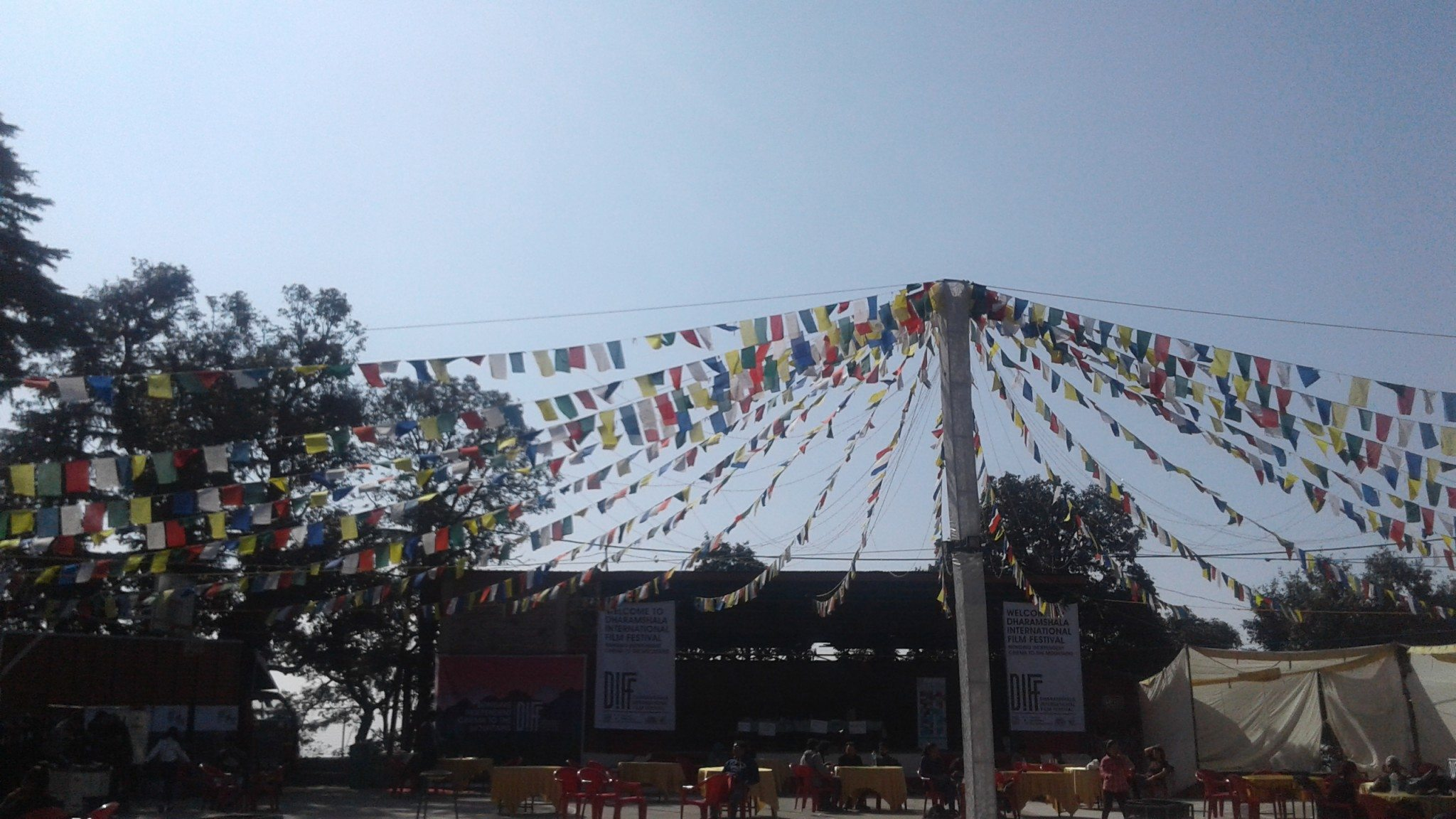 Buddhist prayer flags hanging from a tall pole in the centre of a courtyard with a stage in the background.