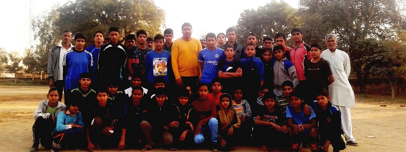 Young and teenage children pose for a picture in a playground with their coach and guardians.
