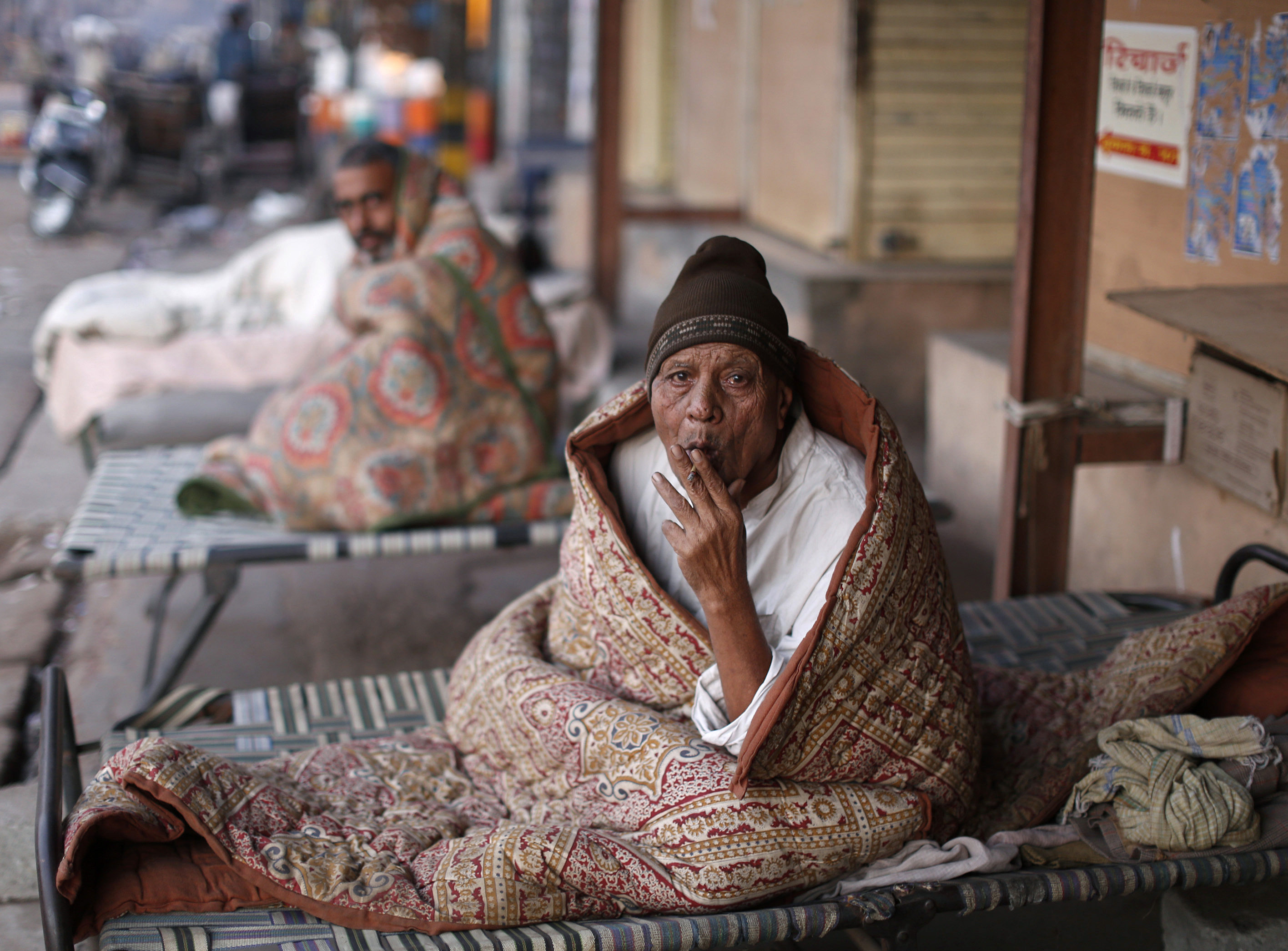 A homeless man smokes as he is wrapped in a quilt at a pavement early morning in the old quarters of Delhi November 27, 2013. REUTERS/Ahmad Masood (INDIA - Tags: SOCIETY) - RTX15UKC