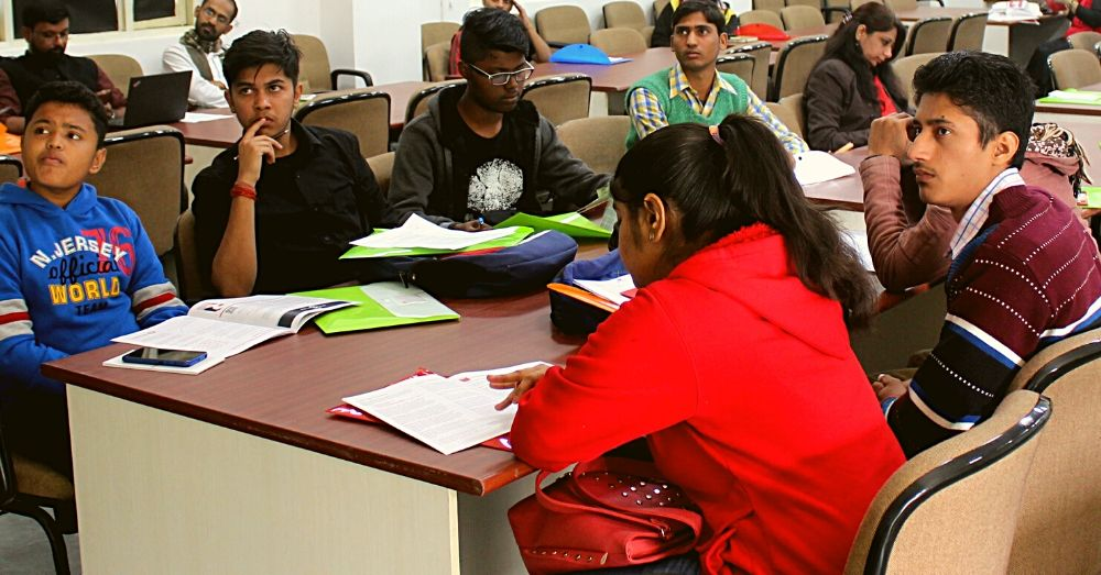 Students sit together at a long desk with books and papers. Image for representation only. Source: Wikimedia Commons