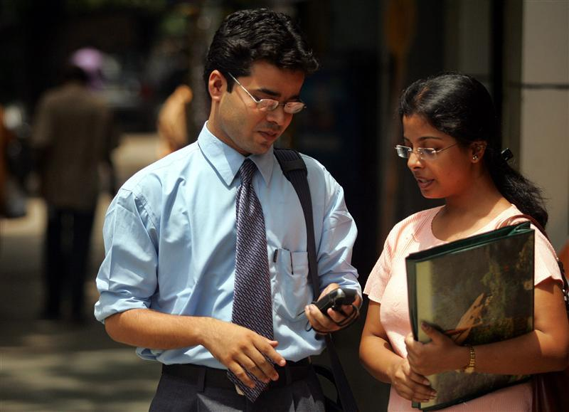 Indian students look at text message from mobile phone in eastern Indian city Indian city of Kolkata.
