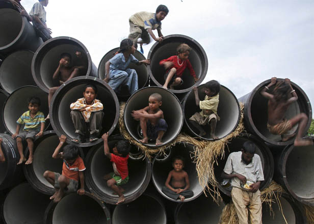 Children play in water pipes at a construction site on the banks of the Yamuna River in the northern Indian city of Allahabad