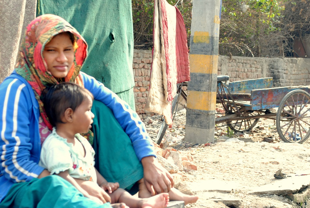 Young mother sitting outside her shack