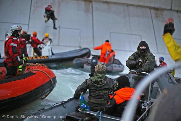 A Russian Coast guard officer points a gun at a Greenpeace International activist as two activists attempted to climb a Gazprom oil platform to hang a banner