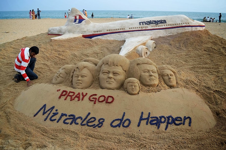 Indian sand artist Sudarshan Patnaik applies the final touches to a sand art sculpture he created for passengers of Malaysian Airlines flight MH370.