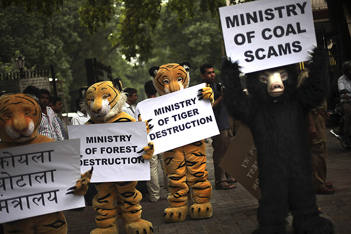 New Delhi, India: Greenpeace activists dressed as animals hold placards