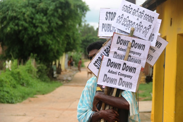 A villager in Machhakuta, central Orissa, carries signs in Odiya and English as he prepares for a protest against Adani Enterprises, the industrial conglomerate contracted to remove nine villages including his to start a coal mine