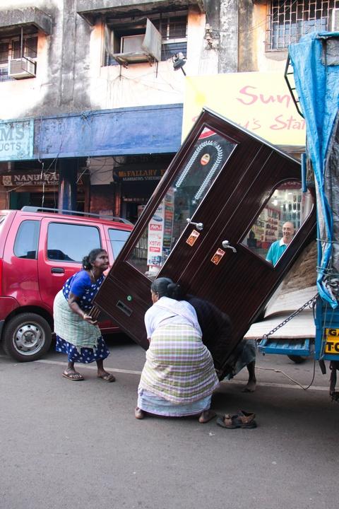 The Bhadel women hauling a steel cupboard