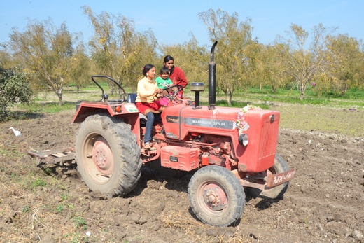 Rippi, 30, (left) and Karamvir, 24, (extreme right) ride their tractor on the farm they inherited from their father in Rajasthan's Kota district. They have overcome hostility to be successful farmers. Photo Credits: Khabar Lahariya