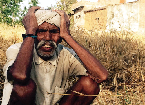 Dev Joo (90) from Lalitpur district's Rajwada village, Uttar Pradesh, sits amid the remnants of his four-acre wheat farm. All the crop was lost to untimely rain and hail. Image: Bhasker Tripathi, Gaon Connection