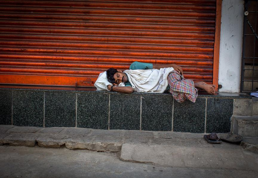 A labourer sleeps around 9.50 am after not finding any work for the day
