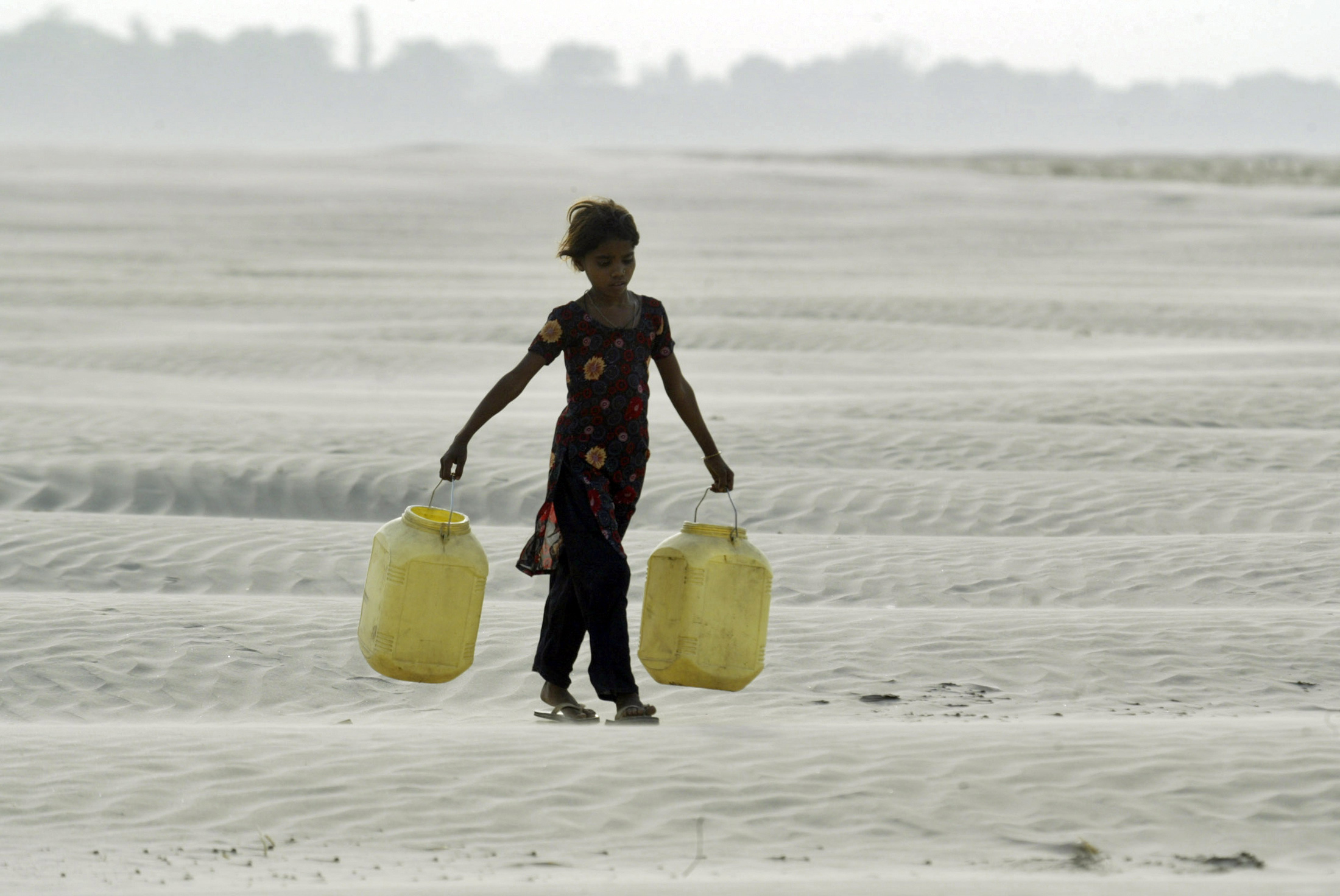 A village girl carries empty containers to collect drinking water near Chilla village in the Bundelkhand region of the northern Indian state of Uttar Pradesh. Image source: REUTERS/Pawan Kumar