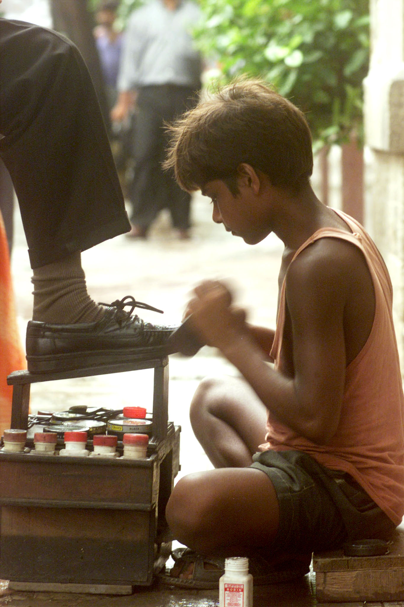 Student Mahesh Das polishes shoes on a pavement in the eastern Indian city Calcutta June 5. Mahesh supports his family and backs his education by earning 20 to 30 rupees a day which is less than a dollar. An estimated 20 percent of Calcutta's 12 milion people live in dire poverty. JS/DL - RTR4ZDS