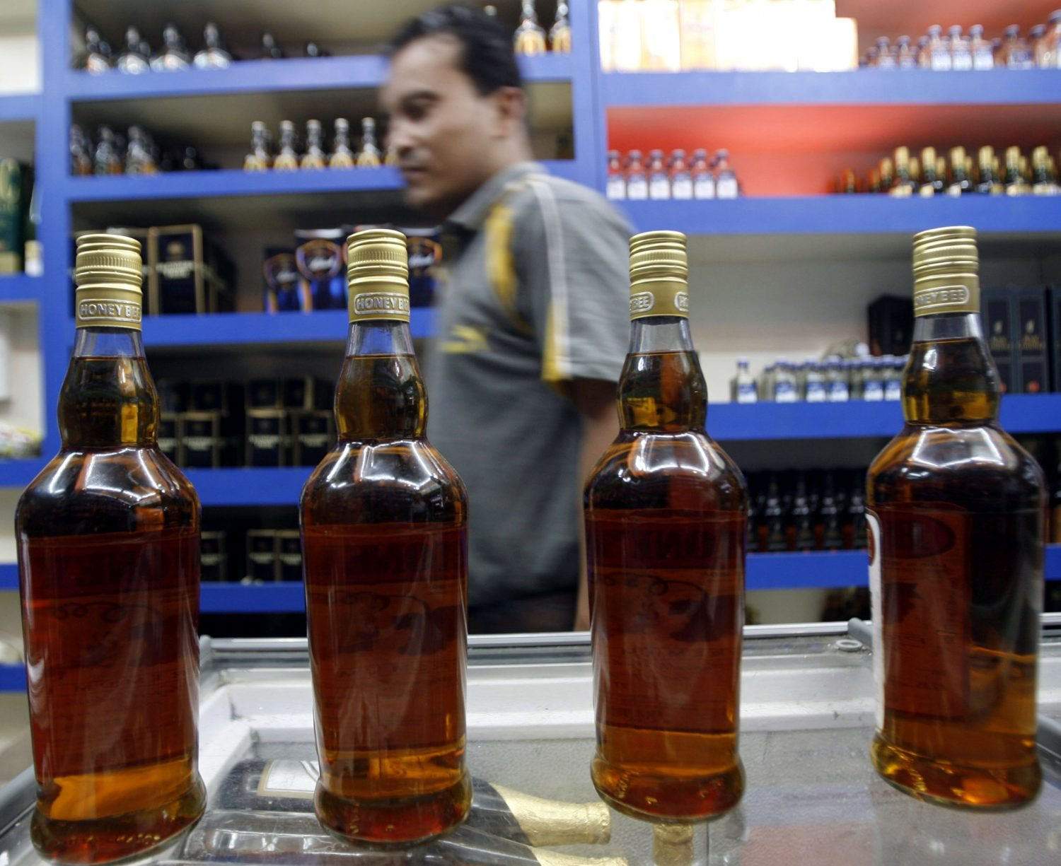 A man walks past bottles of brandy inside a shop selling alcohol in the northeastern Indian city of Siliguri August 19, 2008. REUTERS/Rupak De Chowdhuri (INDIA) - RTR21EMM