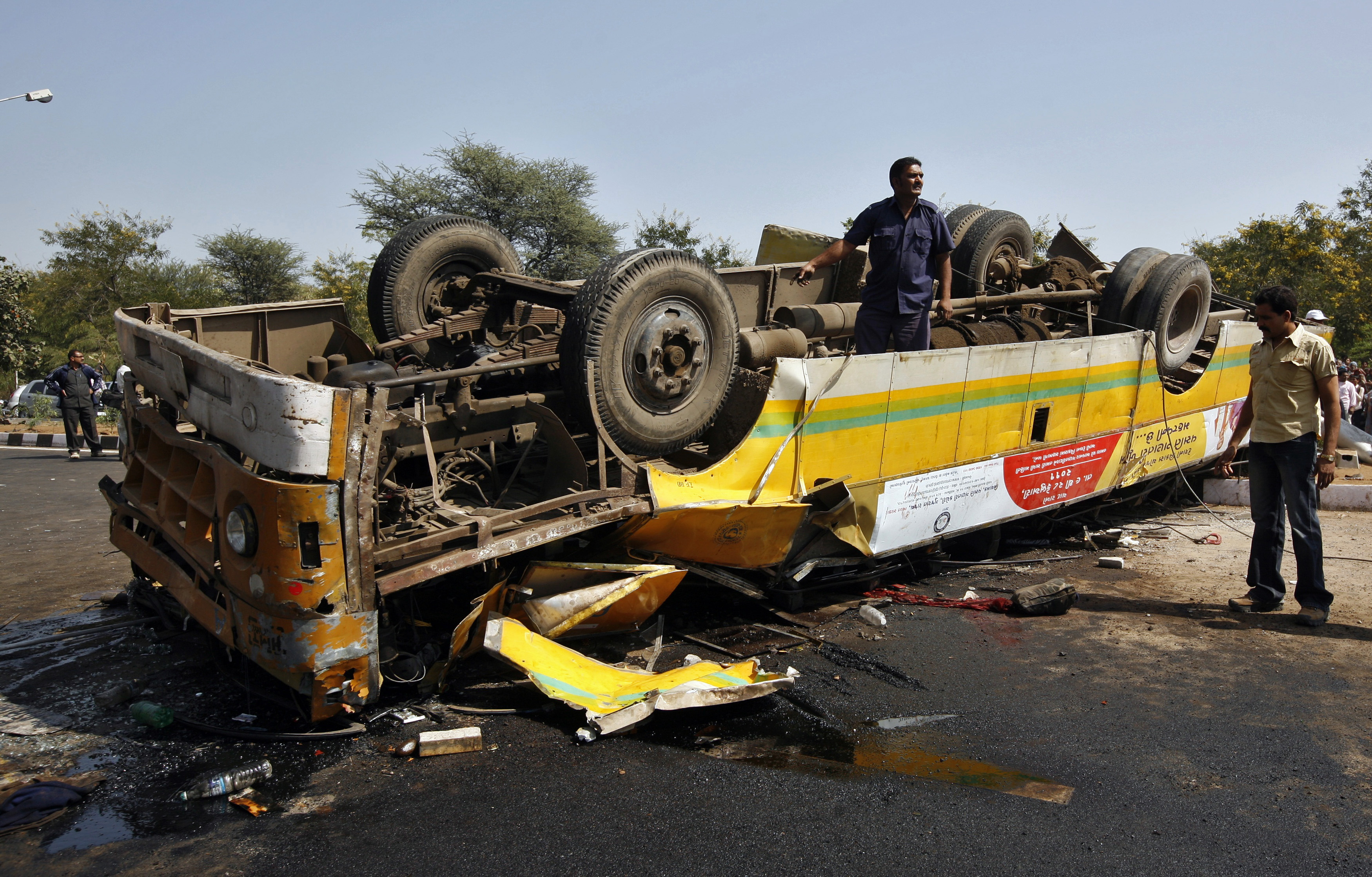 A rescue worker from the Gujarat State Disaster Management Authority (GSDMA) stands on an overturned damaged passenger bus after an accident at Gandhinagar in the western Indian state of Gujarat February 11, 2011. At least two people died and 13 others were injured after the passenger bus they were travelling in collided with a truck, police said on Friday. REUTERS/Amit Dave (INDIA - Tags: DISASTER TRANSPORT) - RTXXQ26