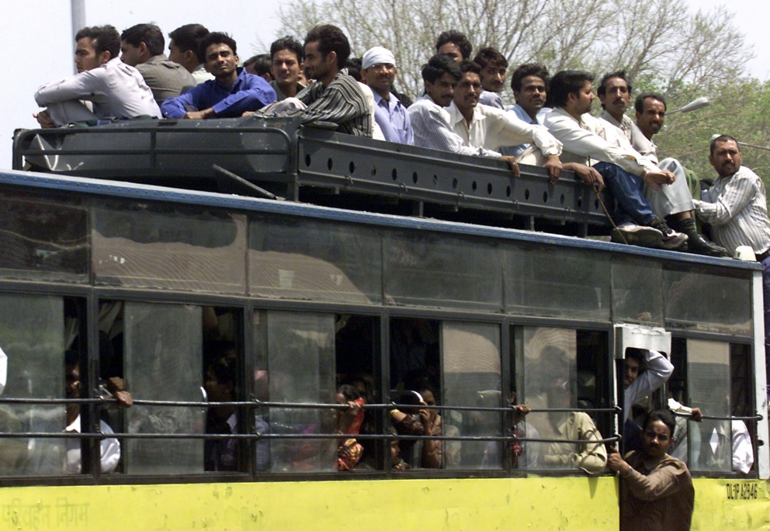 Indians sit on the roof of a overloaded bus in New Delhi April 2, 2001. Commuters in the Indian capital were stranded for a second day running on Monday as thousands of buses and taxis went off the roads under a court order to switch to cleaner fuel. Some 15,000 private and state-run buses and thousands of taxis and three-wheelers had been ordered by the Supreme Court to change to compressed natural gas from diesel by April 1 in a drive to clean the capital's dirty air. PK/JD - RTR13OCB