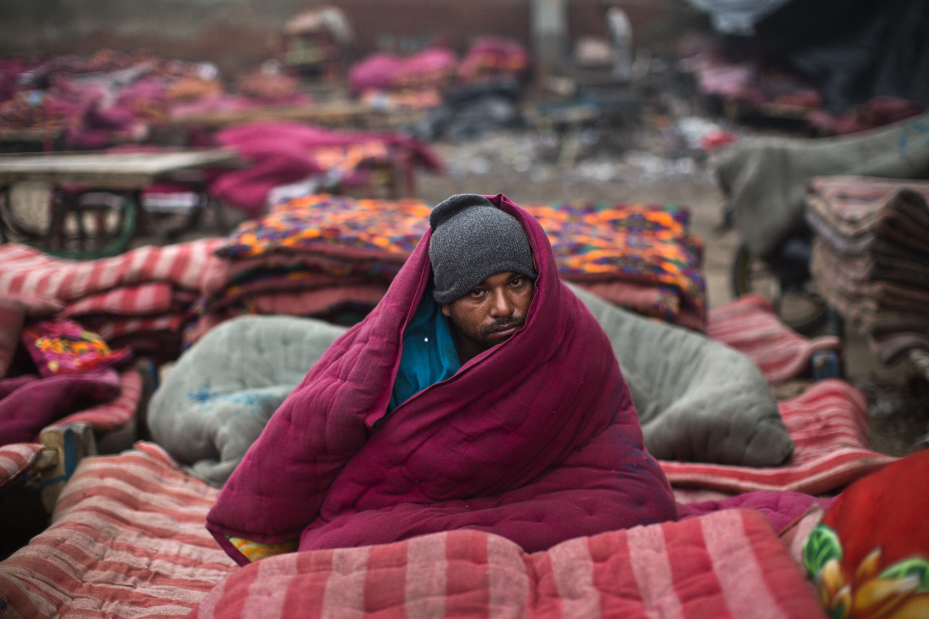 A homeless man, wrapped in a quilt, sits in an open space on a cold winter morning in the old quarters of Delhi January 3, 2013. Heavy fog and a cold wave in Northern India have disrupted life in a number of cities, killing scores of homeless in the state of Uttar Pradesh, as the temperature dipped to around 4 degrees Celsius (39.2 degrees Fahrenheit). REUTERS/Ahmad Masood (INDIA - Tags: ENVIRONMENT SOCIETY POVERTY) - RTR3C2D6