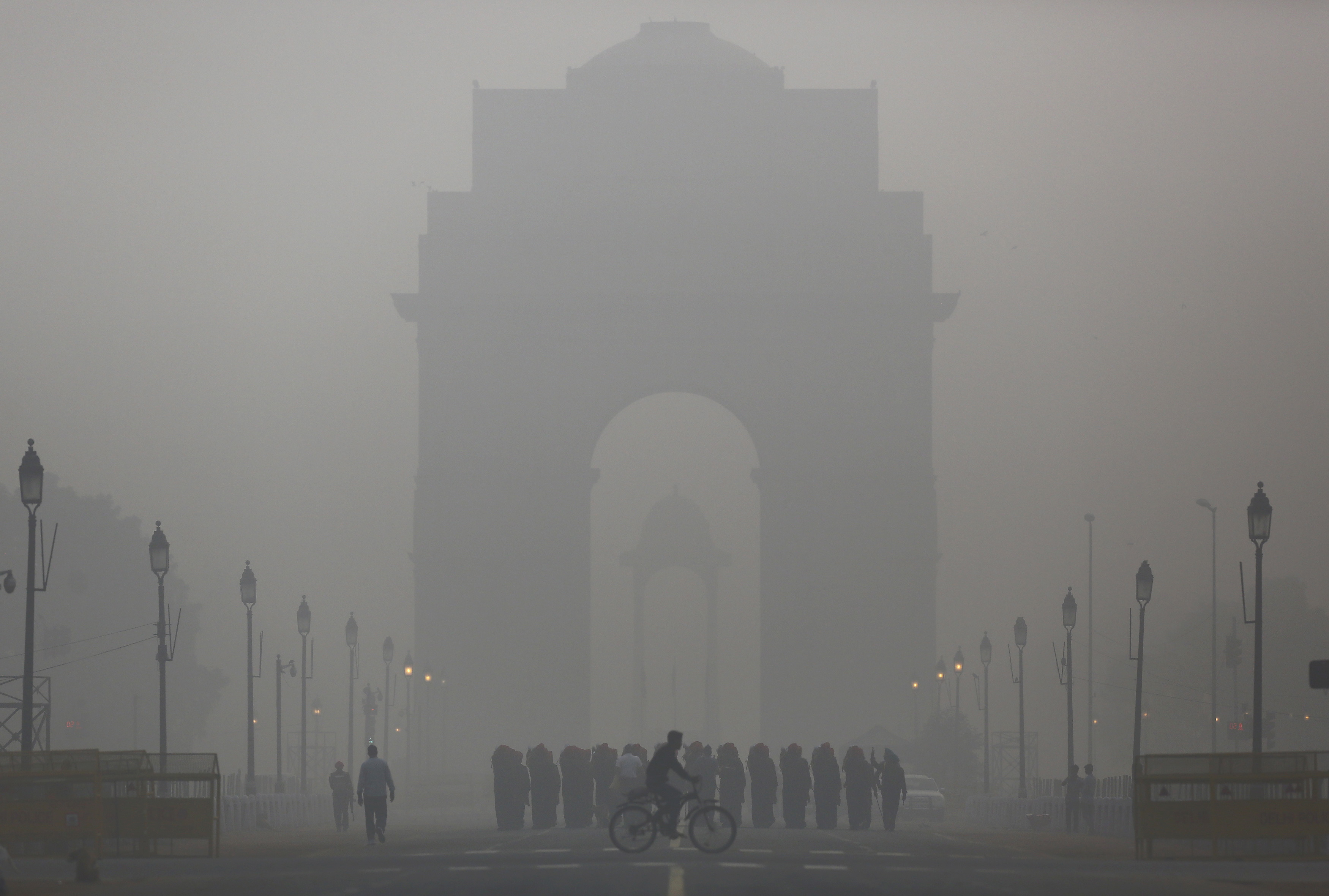 A man rides his bicycle next to Indian soldiers marching in front of India Gate on a smoggy morning in New Delhi, India, December 1, 2015. REUTERS/Anindito Mukherjee      TPX IMAGES OF THE DAY      - RTX1WNKV