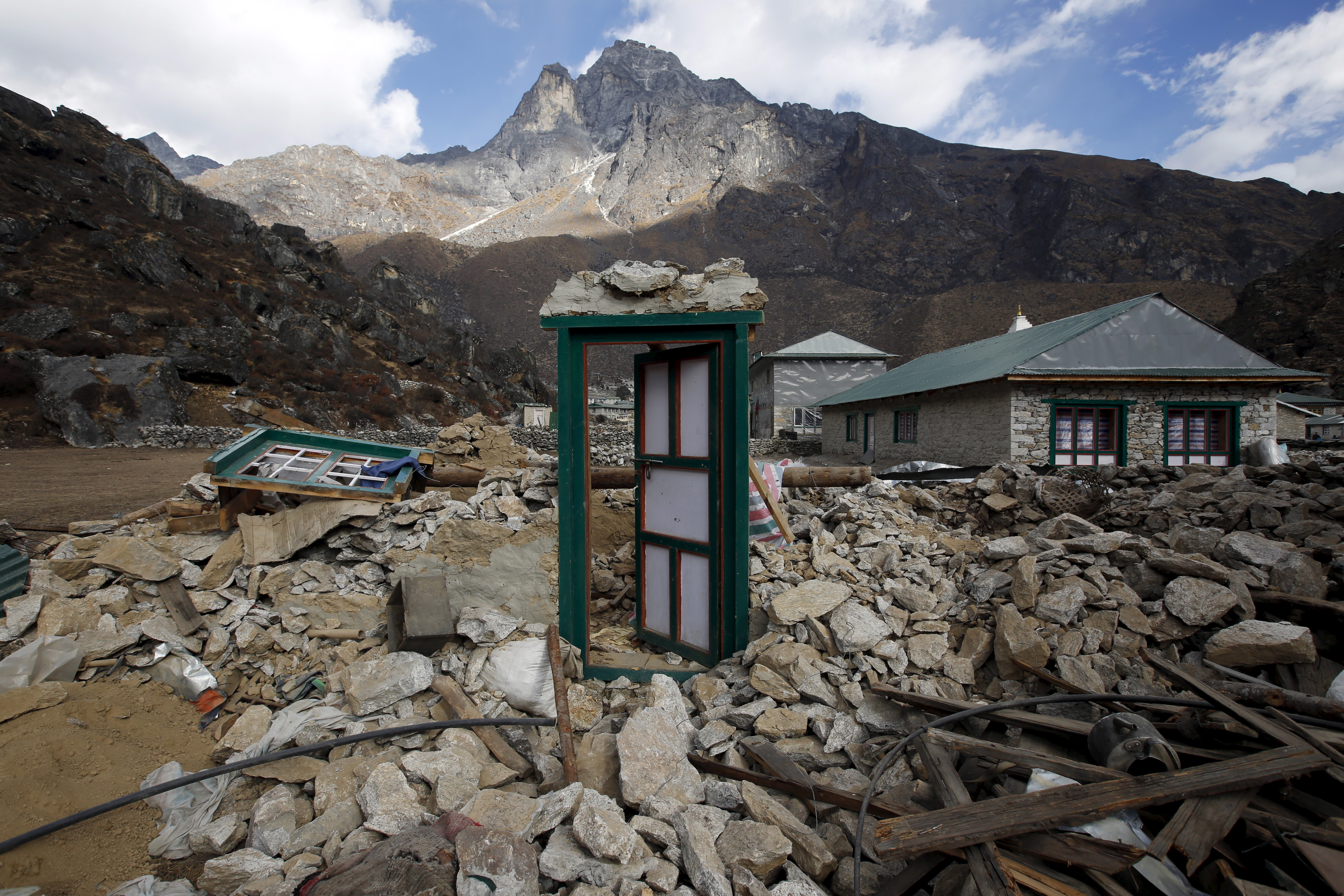 A door of a collapsed house stands after the earthquake damaged it earlier this year at Khumjung, a typical Sherpa village in Solukhumbu district also known as the Everest region, in this picture taken November 30, 2015. To match Insight QUAKE-NEPAL/SHERPAS      REUTERS/Navesh Chitrakar  - RTX1ZEXG