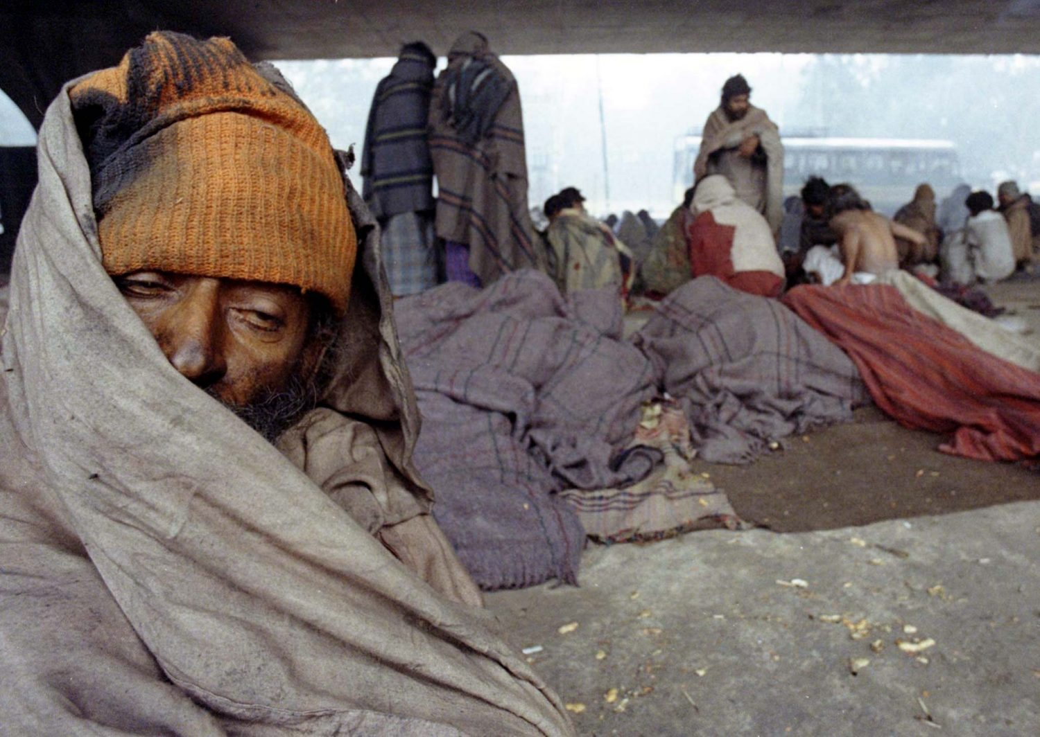 A homeless man tries to get some sleep as he shivers, sitting under a bridge while others like him keep themselves warm in blankets on a biting cold day in New Delhi December 28. Chilly winds and a thick blanket of fog have brought temperatures down to 4.7 degree Celsius, making this winter New Delhi's coldest since 1973. At least 14 people have died in the cold snap which was gripped the entire northwest region of the country. Overcast skies and dense fog have also delayed both incoming and outgoing flights for the past three weeks. INDIA - RTR9XK5