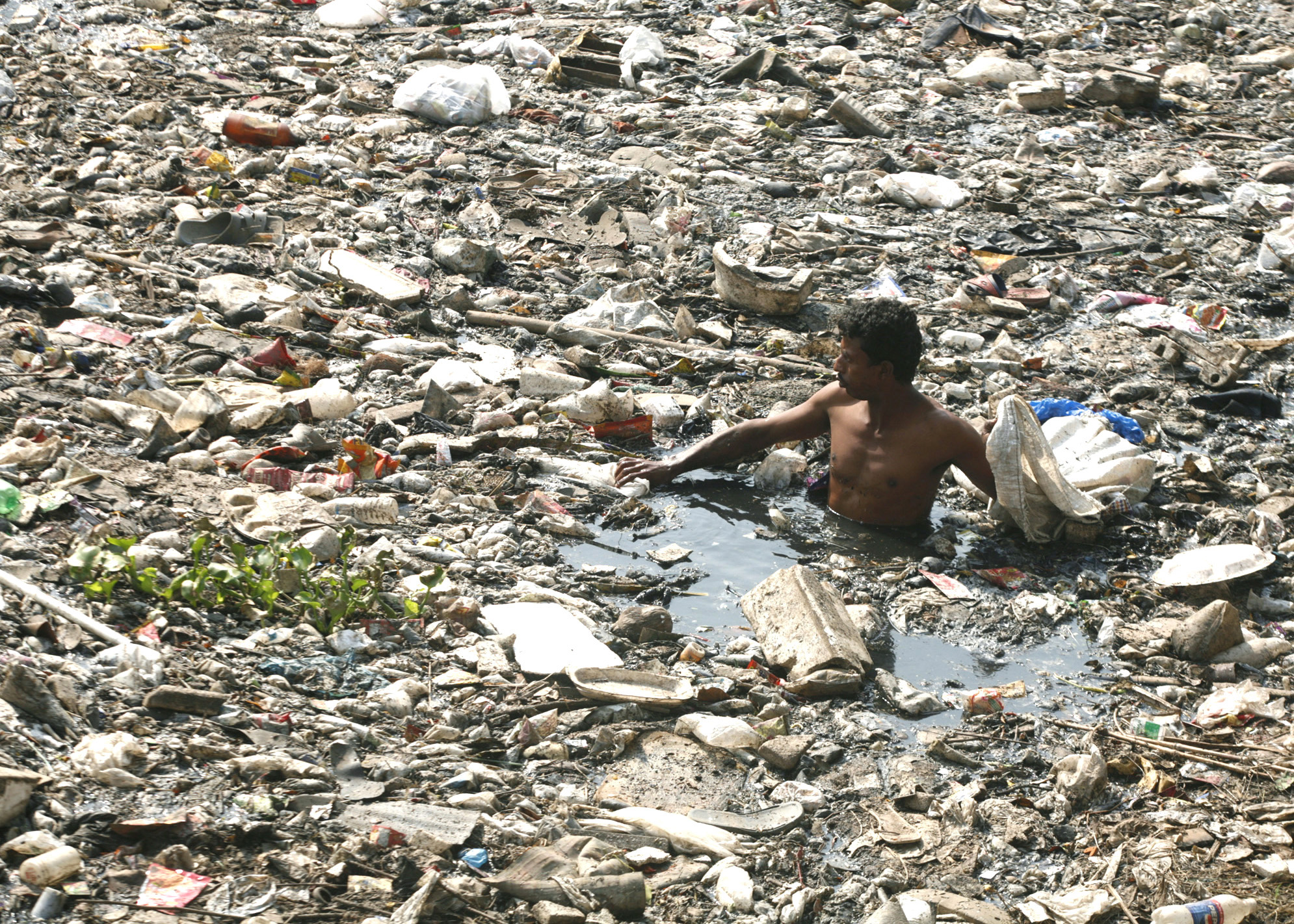 A man scavenges for plastic bags at an open drain in Mumbai February 22, 2007. REUTERS/Prashanth Vishwanathan (INDIA) - RTR1MP23