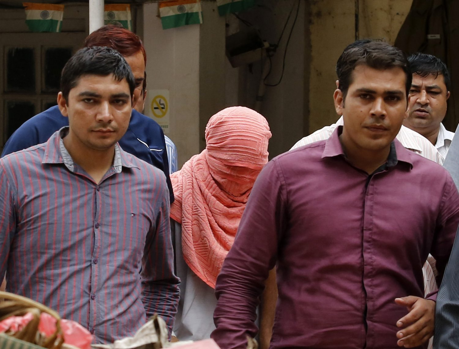 Plainclothes policemen escort an Indian teenager (head covered with towel) after he was sentenced at a juvenile court in New Delhi August 31, 2013. The Indian teenager was sentenced to three years in juvenile detention on Saturday for the December gang rape of a trainee physiotherapist, the first verdict in a case that sparked debate over whether India was too soft on young offenders. REUTERS/Anindito Mukherjee (INDIA - Tags: CRIME LAW TPX IMAGES OF THE DAY) - RTX132GG