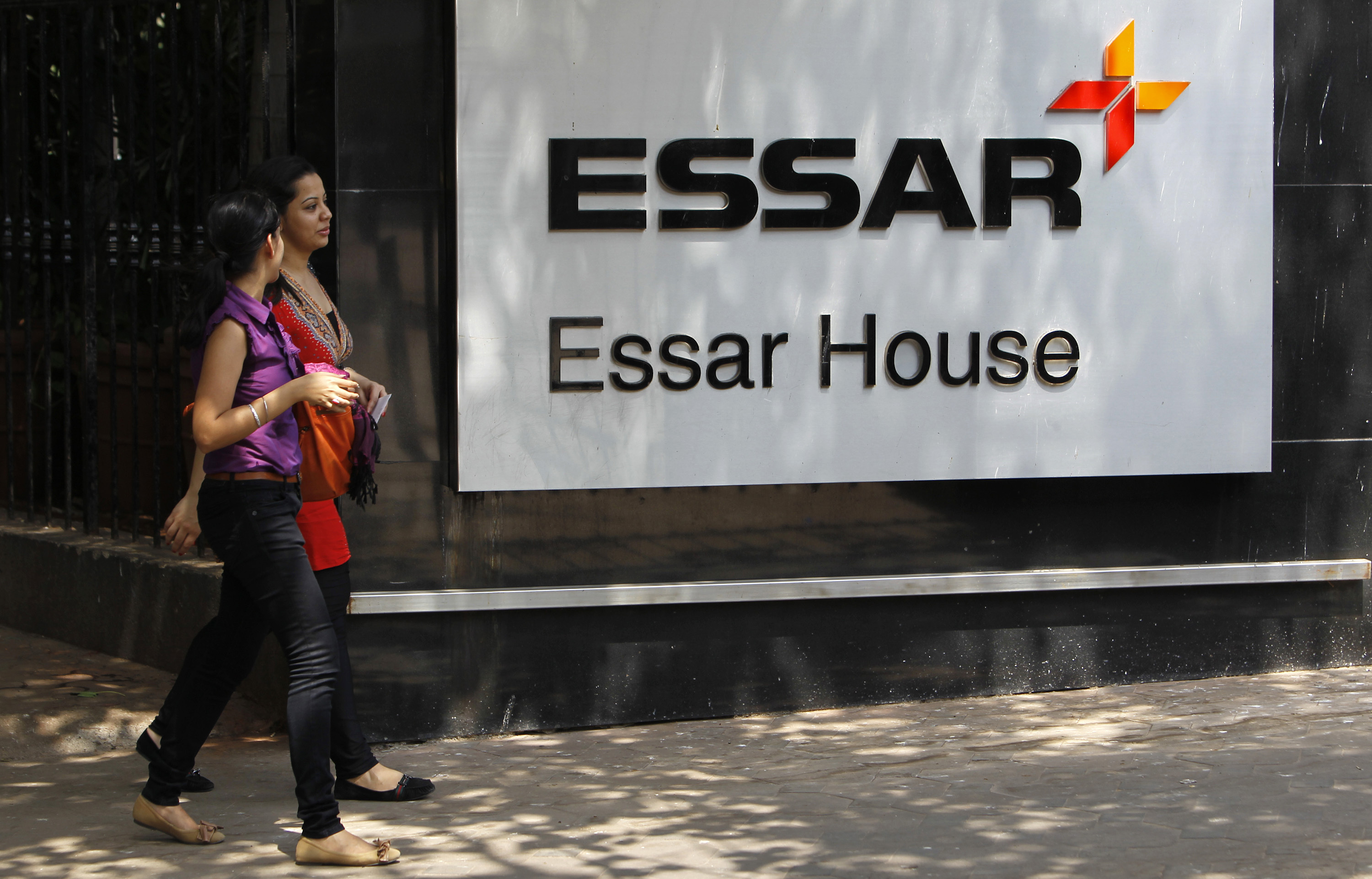 Employees walk past an Essar Group logo outside their headquarters in Mumbai May 20, 2013. India's Economic Times newspaper said the Essar Group conglomerate would sign a financial agreement with China's China Development Bank and China's largest oil and gas producer PetroChina Company during Chinese Premier Li Keqiang's trip to India. REUTERS/Vivek Prakash (INDIA - Tags: BUSINESS LOGO ENERGY POLITICS) - RTXZTPP