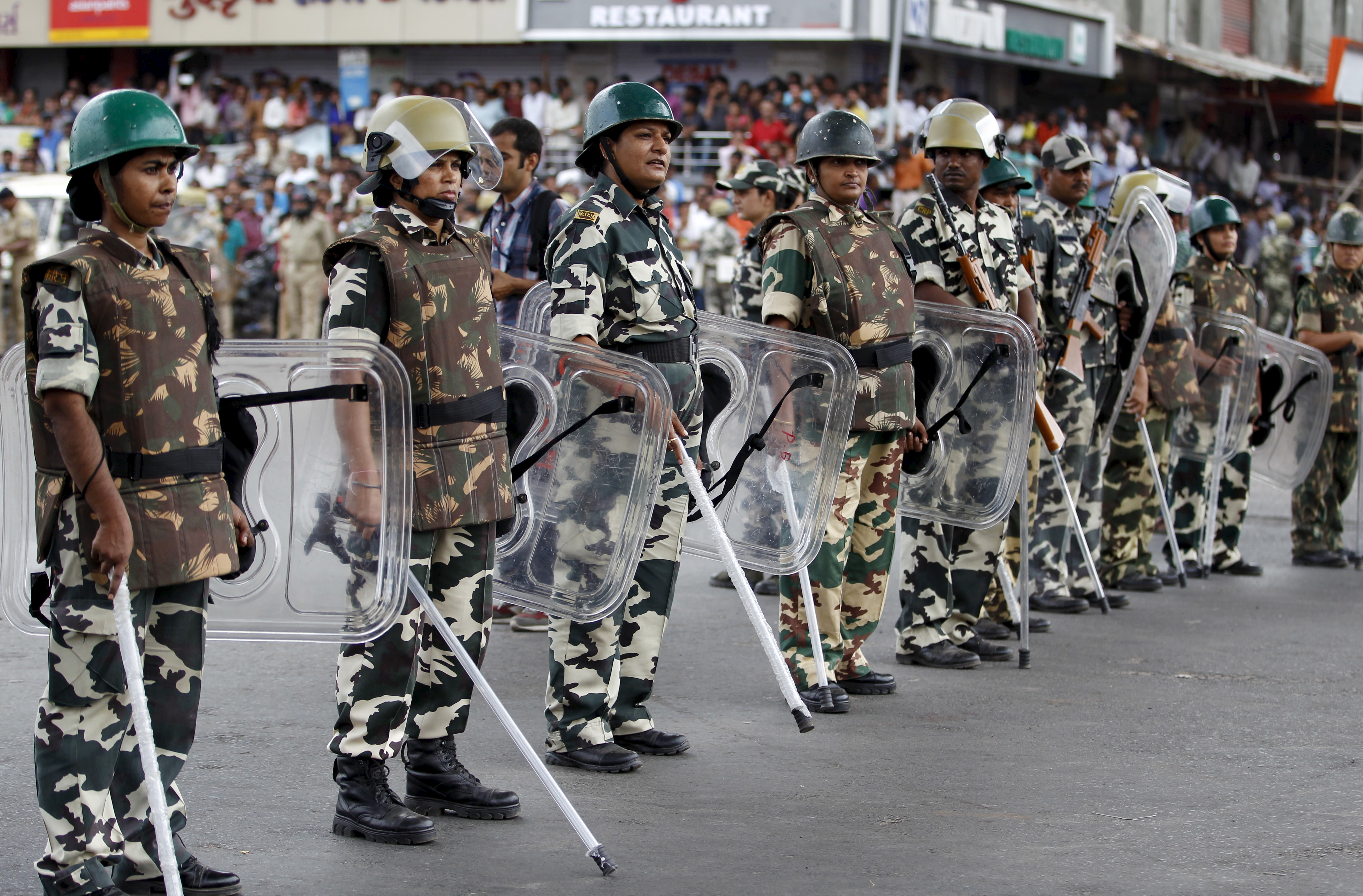 Paramilitary troopers stand guard during the funeral procession of Shwetang Patel in Ahmedabad, India, August 30, 2015. An Indian court in Gujarat state ordered crime investigators on Friday to investigate the death of 32-year old Patel, who allegedly died in police custody after he was taken away by the police during a protest. According to family members, Patel was picked up by police from his home in Bapunagar area after violence broke out in the state following a mammoth rally by the powerful Patel community seeking reserved jobs and education places.   REUTERS/Amit Dave - RTX1Q8Z1
