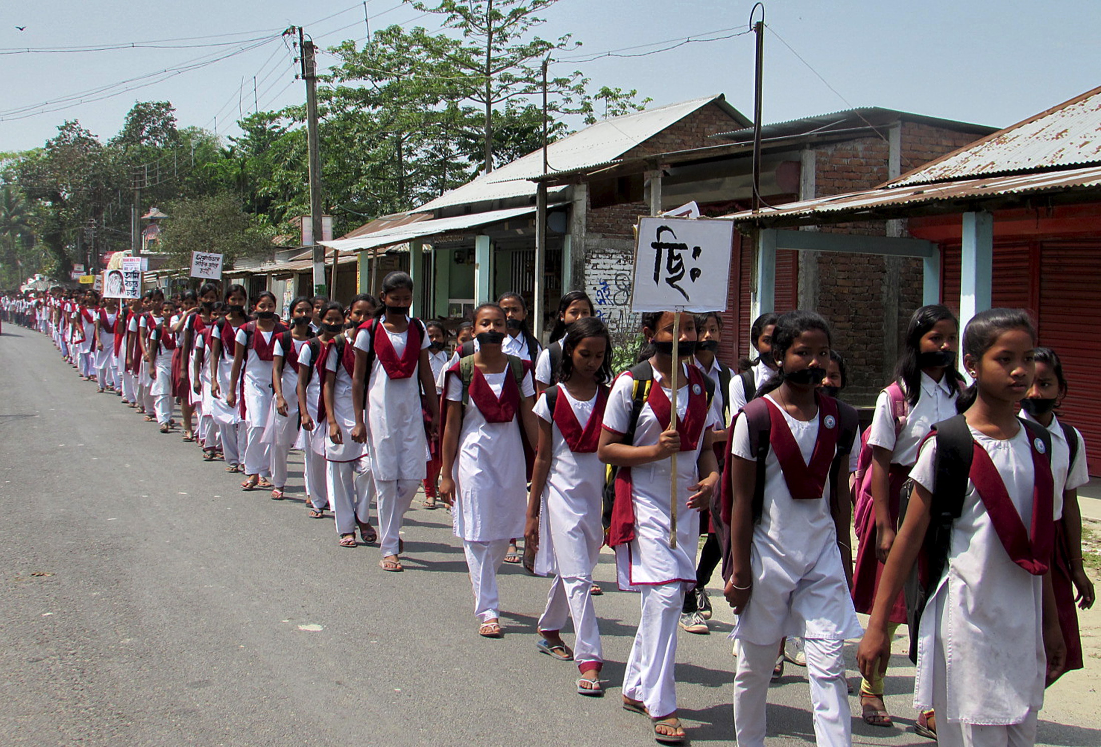 School girls wear black bands on their faces during a protest rally against the rape case of a 16-year-old girl at Dhupguri town in the eastern Indian state of West Bengal, April 11, 2015. The father, uncle and brother of the girl have been arrested accused of raping her repeatedly over a period of two years, police said on Saturday. REUTERS/Stringer - RTR4WWWA