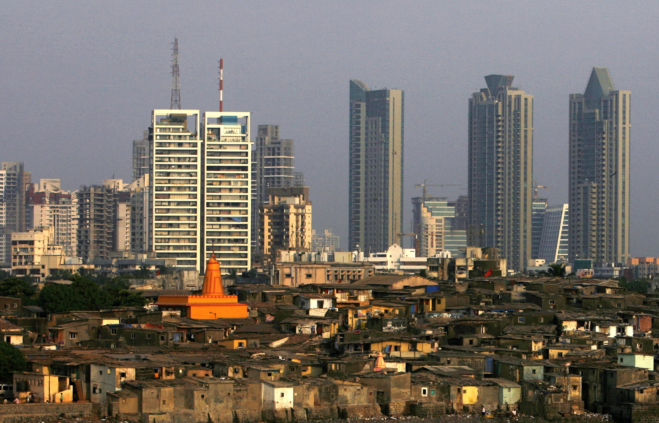 High rise buildings are seen behind a slum in Mumbai April 28, 2009. REUTERS/Arko Datta (INDIA SOCIETY BUSINESS) - RTXEIGM