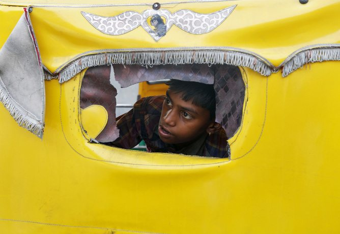 "A boy peeps through a window of an auto rickshaw to watch a protest by India's lowest caste ""Dalits"" in the western Indian city of Ahmedabad April 27, 2014. Dozens of the Dalits on Sunday held a protest outside the venue of a yoga camp in the city demanding action against Indian yoga guru Baba Ramdev for his recent remarks that Dalits said were disrespectful. REUTERS/Amit Dave (INDIA - Tags: POLITICS CIVIL UNREST) - RTR3MTGE"