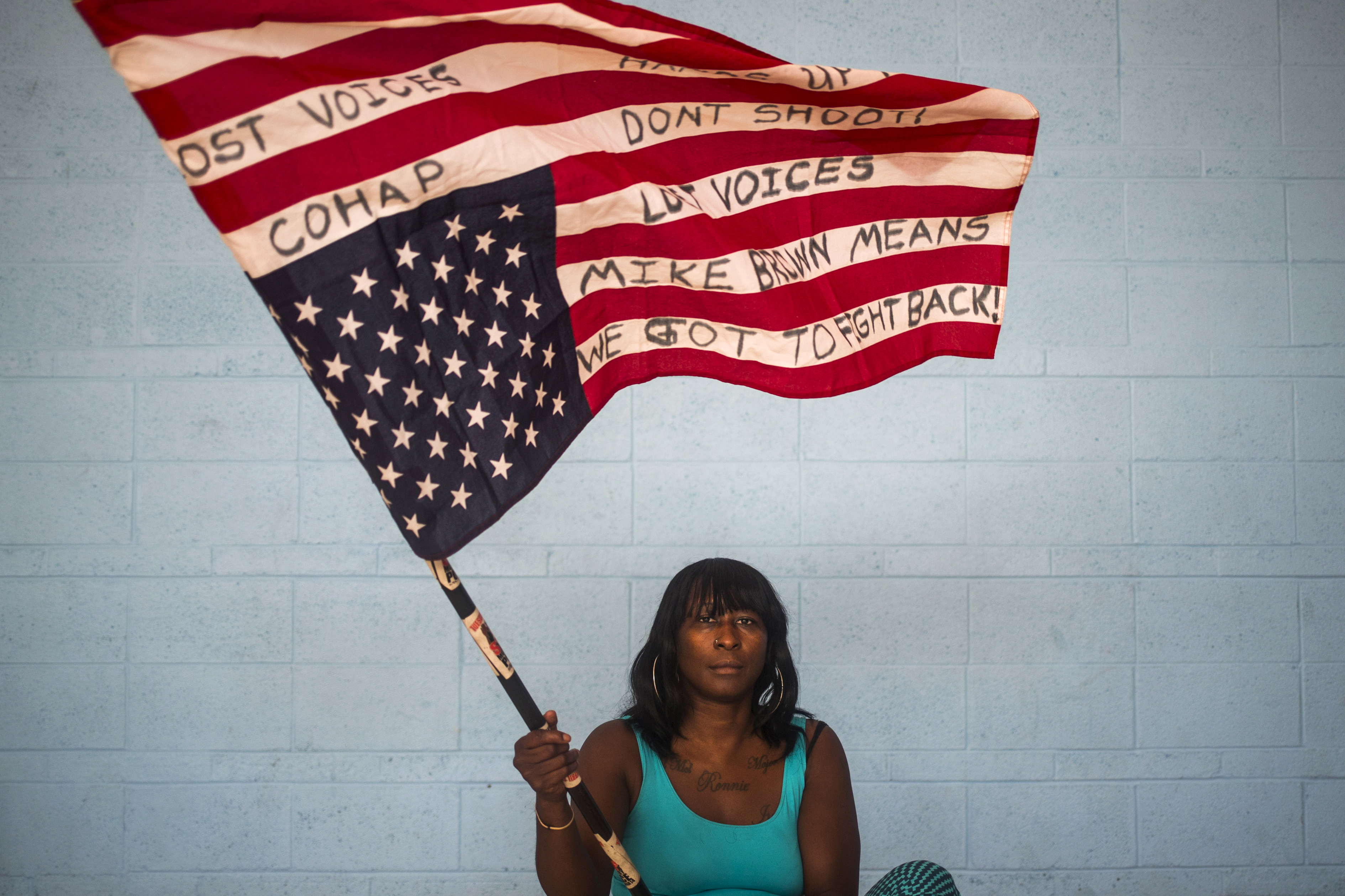 "Chocolate, 36, an activist who wants to be identified by only her nickname, waves an American flag upside down while posing for a portrait in Ferguson, Missouri July 24, 2015. When asked how Michael Brown's death affected her life, Chocolate said, ""My life won't ever be the same. It has changed me to become an activist and protester. It has made me to get more involved with my community and especially with youth. When you ask a kid these days what they want to be when they grow up, their answer is ""I want to be alive."" When asked what changes she has seen in her community over the past year, Chocolate said, ""We are all still trying to heal. There are still a lot of racist cops here. We can do what we do which is stand up for justice. No one has accepted what happened out here. There is still a disconnect with the police and the community."" The message on the flag reads: Hands up, don't shoot. Lost voices. Mike Brown means we got to fight back! On August 9, 2014 a white police officer shot unarmed black teenager Michael Brown dead in the St. Louis suburb of Ferguson, Missouri. A year later Reuters photographer Adrees Latif returned to Ferguson, where he has documented events in the past year, to capture the portraits of local residents and canvass their views. REUTERS/Adrees Latif TPX IMAGES OF THE DAYPICTURE 6 OF 13 FOR WIDER IMAGE STORY ""PORTRAITS OF FERGUSON""SEARCH ""LATIF PORTRAITS"" FOR ALL PICTURES - RTX1N6N6"