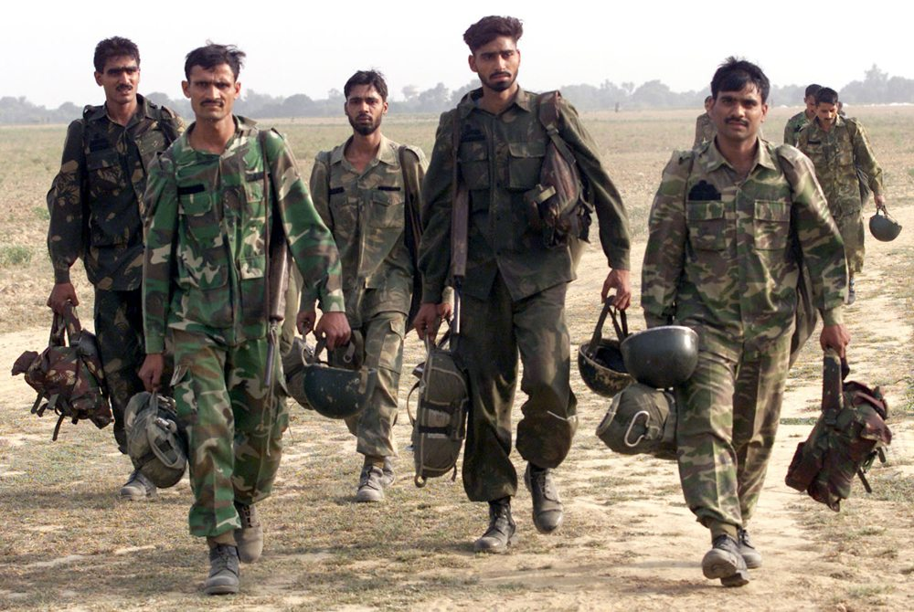 Indian paratroopers walk back to their base after taking part in a joint exercise with U.S. troops at an airforce station near the northern city of Agra October 22, 2002. Indian and U.S. troops for the second time this year took part in a joint military exercise demonstrating growing ties between the world's two largest democracies that once sat on opposite sides during the Cold War. REUTERS/Kamal Kishore JSG/WS - RTRCJQP