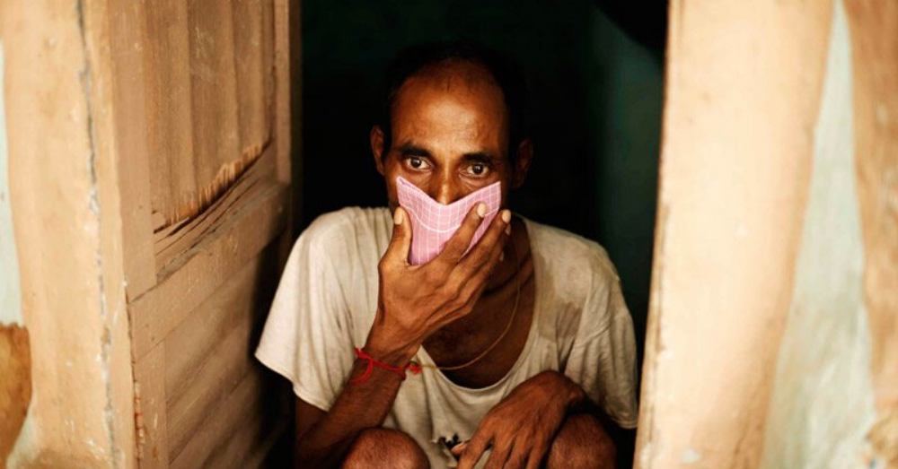 a man covering his mouth with a hankerchief in his hand