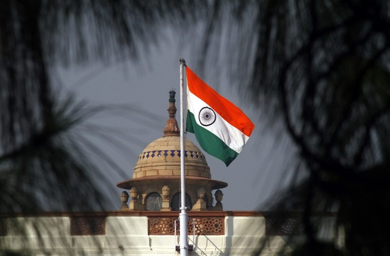An Indian national flag flutters on top of the Indian parliament building in New Delhi December 1, 2010. The Indian parliament on Wednesday approved a $9.8-billion additional spending bill to cover various payments including outstanding government debt, food and fertiliser subsidies, and government pensions. The bill was passed by a voice vote in parliament, a type of vote allowing the government to bypass a three-week deadlock between the ruling Congress party-led coalition and opposition parties caused by rows over a series of corruption scandals. REUTERS/B Mathur (INDIA - Tags: POLITICS BUSINESS) - RTXV9P0