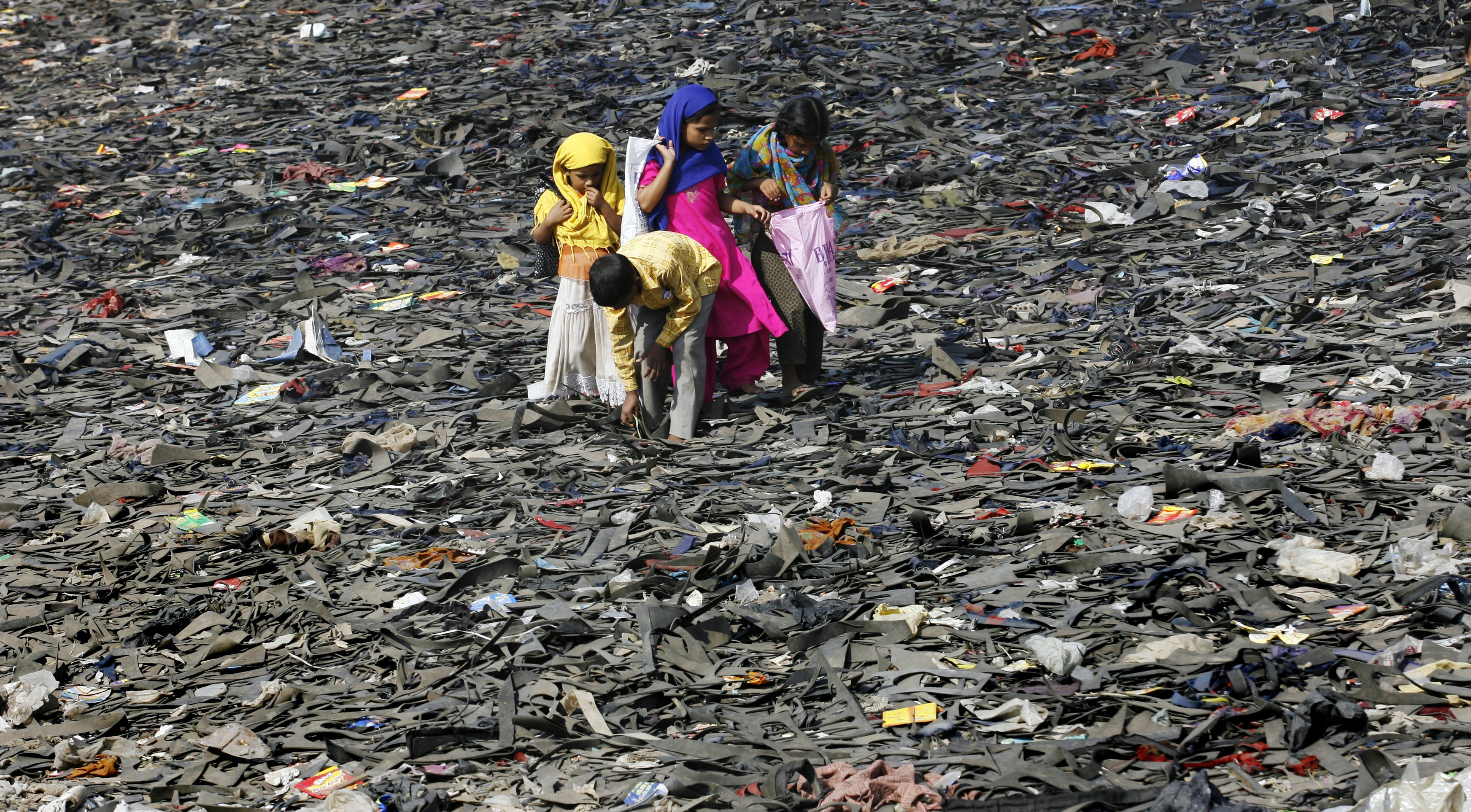 Slum children walk through a dried-up creek covered with wasted rubber sheets in Mumbai November 23, 2009. More than a third of India's population survives on less than one dollar a day, according to a 2007 United Nations report. REUTERS/Arko Datta (INDIA ENVIRONMENT SOCIETY IMAGES OF THE DAY) - RTXR1HE