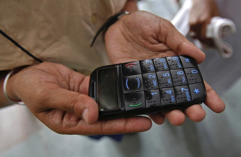A visually impaired girl holds a model of Intex Vision, a mobile phone designed for the visually impaired, during its launch in New Delhi April 19, 2011. The phone has a large Braille keypad to facilitate the recognition of digits. India has the world's largest blind population and the phone is designed to enhance the quality of life of visually impaired people, a media release said. REUTERS/Adnan Abidi (INDIA - Tags: BUSINESS SCI TECH SOCIETY) - RTR2LE83