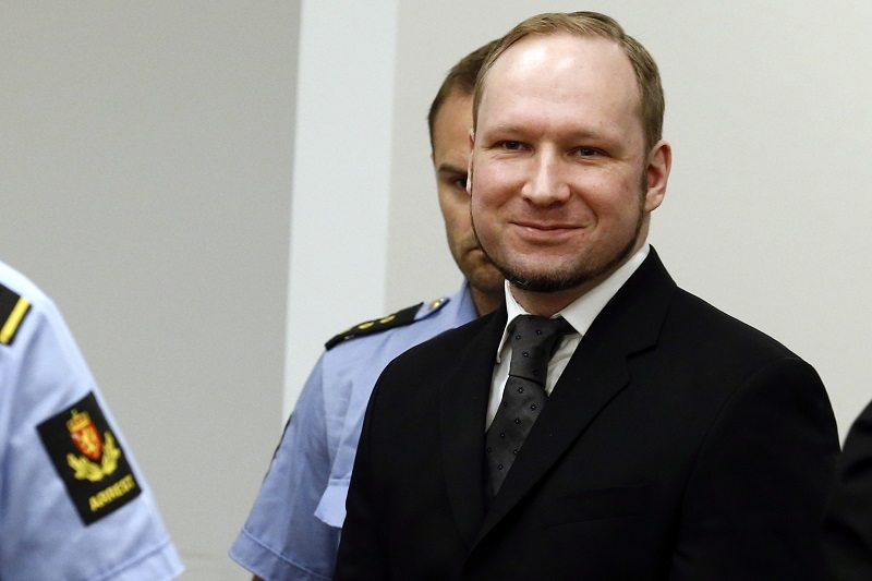 Norwegian mass killer Anders Behring Breivik smiles as he arrives at the court room in Oslo Courthouse August 24, 2012. Breivik was jailed for a maximum term on Friday when judges declared him sane enough to answer for the murder of 77 people last year, drawing a smirk of triumph from the self-styled warrior against Islam. REUTERS/Heiko Junge/NTB Scanpix/Pool (NORWAY - Tags: CRIME LAW) - RTR372Y1