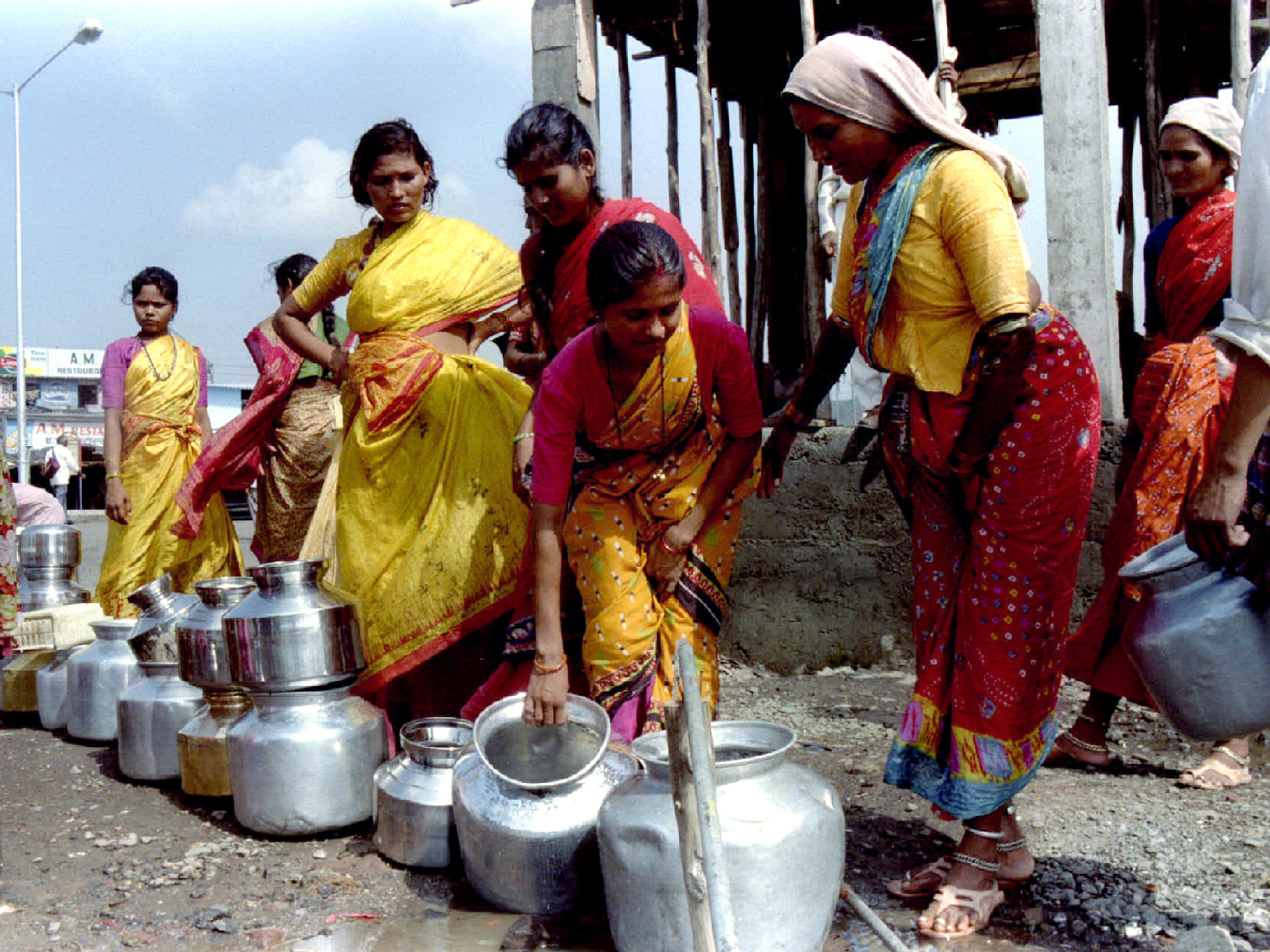 Women in Bombay line up vessels to fill water from a pipe June 23 as the delay in the monsoon has resulted in an acute shortage of water. The water supply in the city comes from nearby lakes which depend mainly on the four month monsoon rains between June and September.