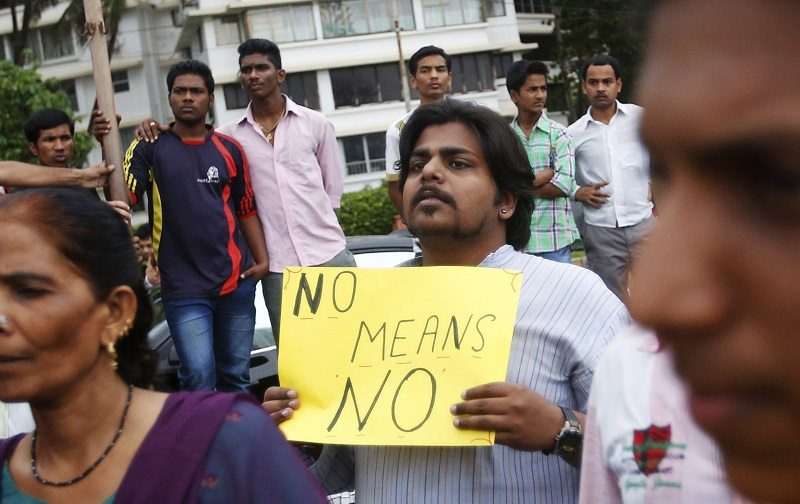 A man holds a placard during a silent rally to protest against the rape of a photo journalist by five men in Mumbai August 25, 2013. Indian police have arrested all five suspects in connection with the gang-rape of a photo journalist in Mumbai last week, a senior official said on Sunday, in a case that has revived uncomfortable questions about women's safety. REUTERS/Danish Siddiqui (INDIA - Tags: CRIME LAW CIVIL UNREST) - RTX12W0M