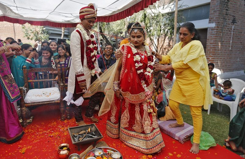 Family members help a visually impaired couple to navigate around the ceremonial fire as they take their vow during their wedding ceremony in Ahmedabad, India, January 24, 2016. Four visually impaired couples tied the knot in a traditional Hindu and Muslim marriage ceremony in western India on Sunday, arranged by an educational institute that helps better integrate the visually impaired into society, organisers said. REUTERS/Amit Dave - RTX23S99