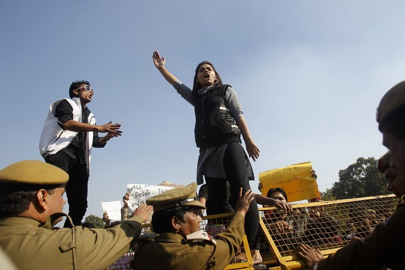 A demonstrator standing on a barricade erected by police shouts slogans during a protest rally organised by various women's organisations in New Delhi December 21, 2012. Thousands of protesters took to the streets in various parts of the country to demand urgent action against the men who took turns to rape a 23-year-old woman on a moving bus on December 16, local media reports said. REUTERS/Mansi Thapliyal (INDIA - Tags: CRIME LAW CIVIL UNREST) - RTR3BT7J